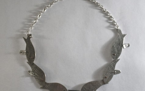 Necklace designed to look like multiple fish. Zoe Prekop crafted it in Metalsmithing to later on submit to an art show. This piece won her a scholarship.