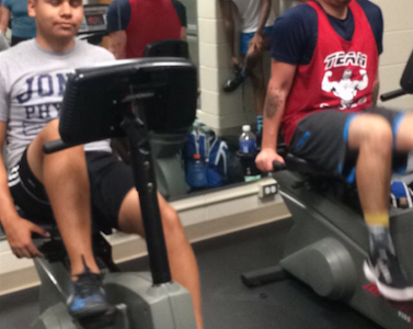 Israel Reyez '16 and Art Teacher Gaberiel Dominguez work on cardio at the former classroom turned fitness center in the north building.