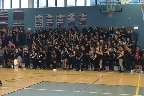Seniors, dressed in black, lead cheers against other classes in the gym during the Eagle Games.