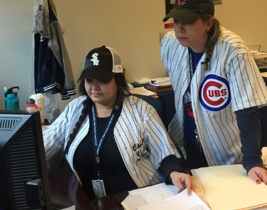 Meredith Kramer (R) and Erma Gamboa (L) wear their team jerseys in the office.