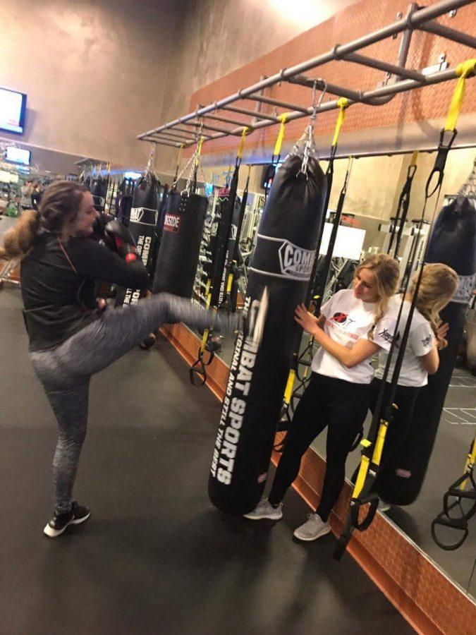 Victoria Gnat '17 and a client work on their kickboxing skills.