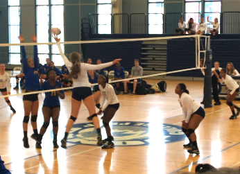Jill Kavalauskas '18 tips the volleyball over Lincoln Park's blockers, scoring a point and further widening the lead during Tuesday night's blowout against Lincoln Park.
