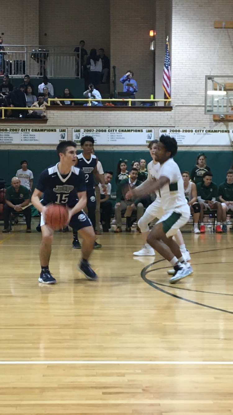 Niko Rosich '21 passes the ball at the top of the key.