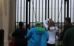 Parents attempt to get a glimpse of the competition inside Lane Tech field after being forced outside due to COVID-19 protocol.